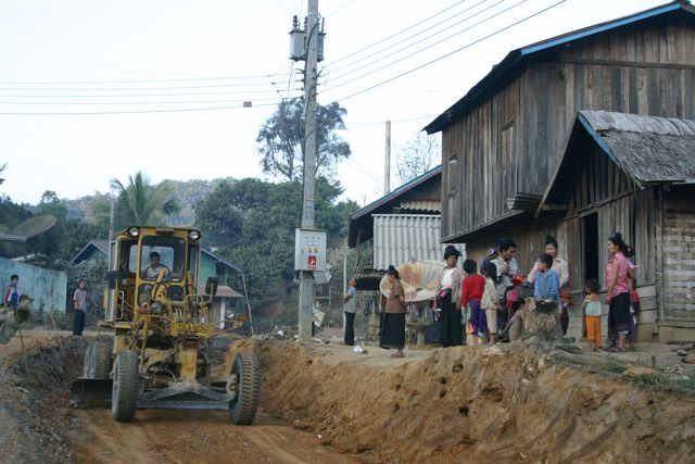 Project Phongsali 2011: Equipment rumbles through town known to have bombs.  Children dig in uncleared soil.